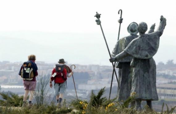 Un par de peregrinos dejan atrás una bella escultura