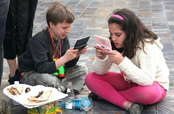 Dos niños jugando a la consola en la calle